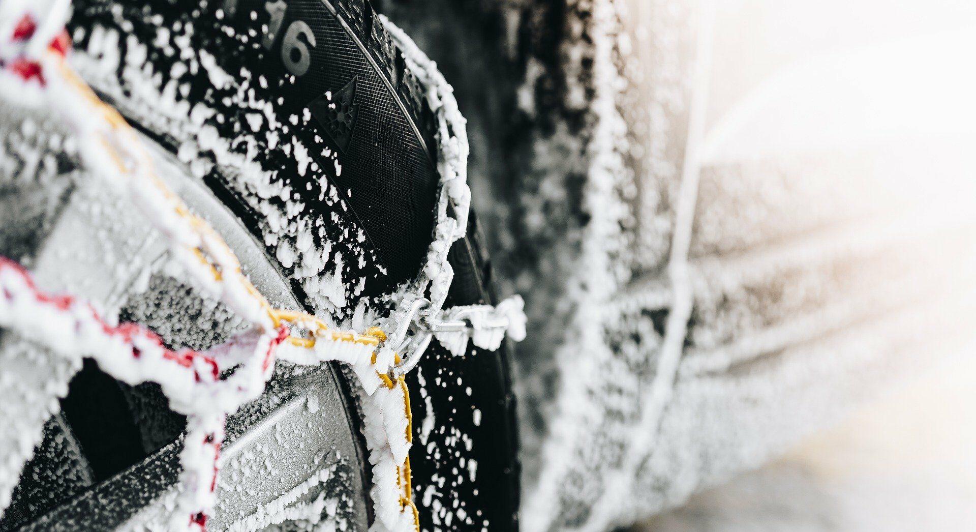 Pneu hiver avec des chaînes couvert de neige